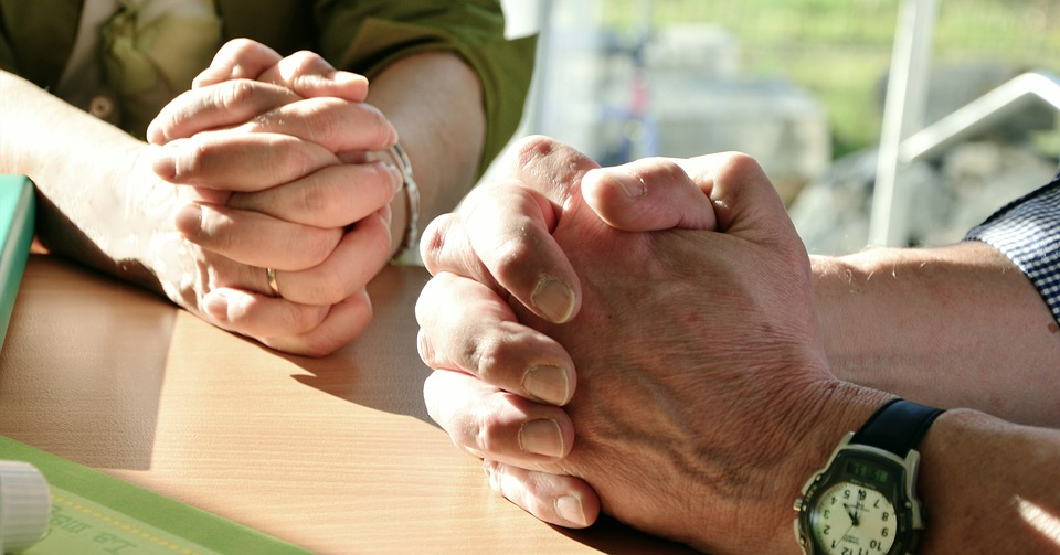 Two hands are folded in prayer.